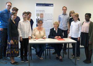 Frau Dr. Heike Schroll und Frau Etta Ites-Pätzold unterzeichnen die Kooperationsvereinbarung. Im Hintergrund Schülerinnen und Schüler des Europäischen Gymnasiums Bertha-von-Suttner.