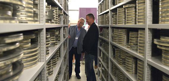 Referatsleiter Thilo Mrosek zeigt Dr. Klaus Lederer, Senator für Kultur und Europa, das Filmmagazin im Landesarchiv Berlin. Foto: Thomas Platow